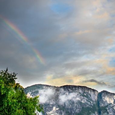I was at the right place at the right time to catch the rainbow above the granite, of the Squamish Chief. From right to left, head, torso, legs of Chief laying on his back.