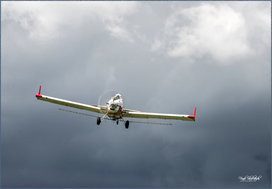 A crop duster at work spraying canola fields in rural southern Alberta, Canada.