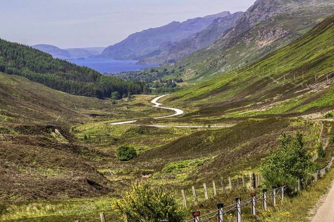 The road leading down to a small loch in the toridans. Part of the scottish highlands.