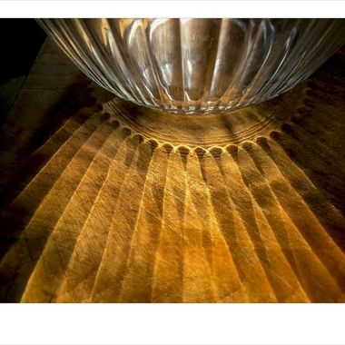 Ornate bowl on cutting board in pantry with streaming sunlight.