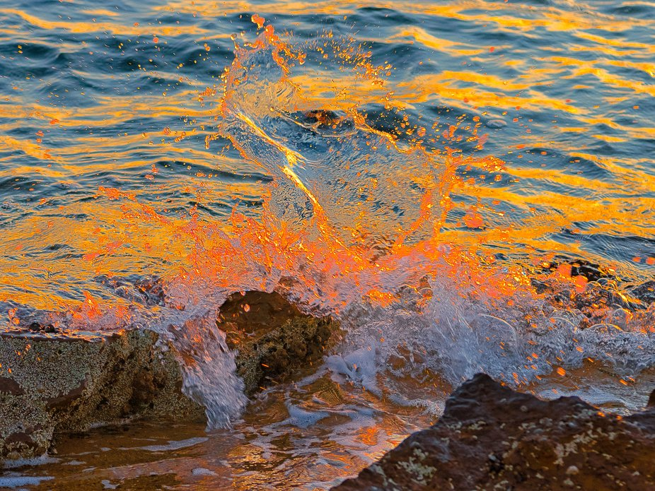 Catching the colours of sunset in the waves and splashes against the rocks at the beach in Half M...