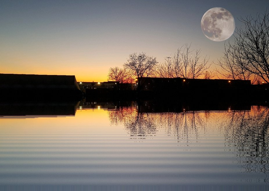 Sports center reflected in water at sunset above the moon