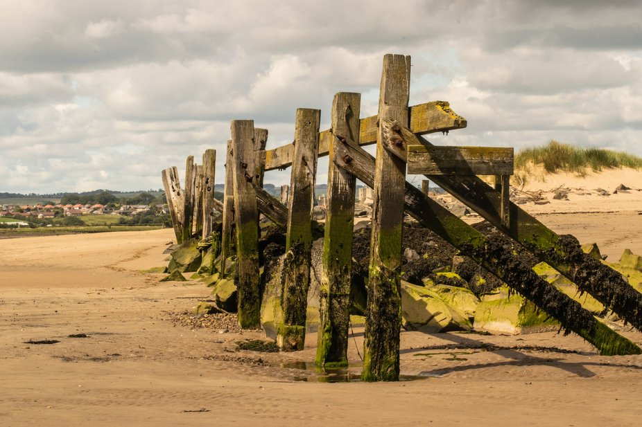 Rotting remains of old coal staithes at Warkworth Northumberland UK