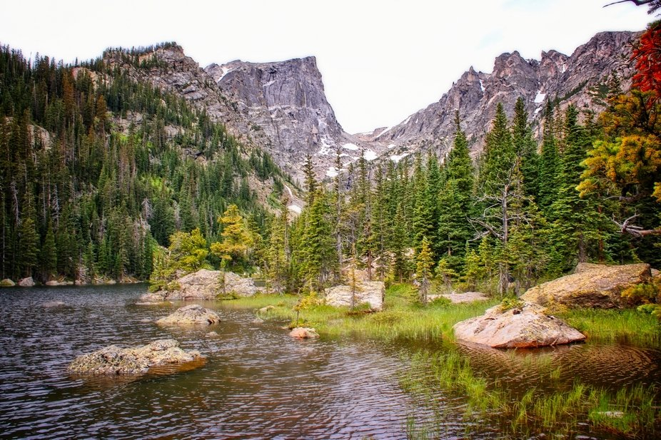 A trail from Bear Lake to Emerald Lake in the Rocky Mountain National Park passes this lake with mountain peaks in the background....