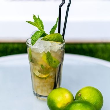 a close up image of a freshly made mojito cocktail on a table with lime garnish