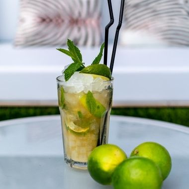 a image of a freshly made mojito cocktail on a table with lime garnish