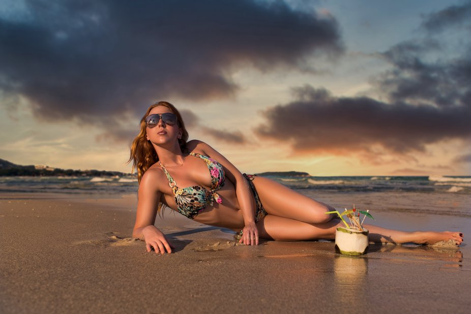 Young beautiful female in the bikini lying on the beach