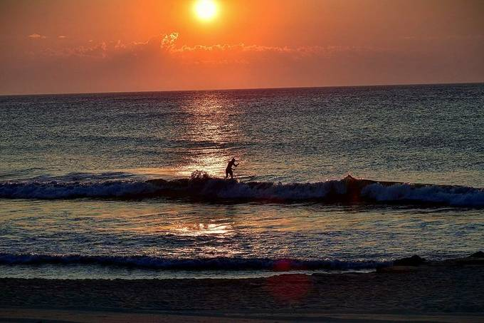 early morning paddler catching some good wave action at the Jersey Shore