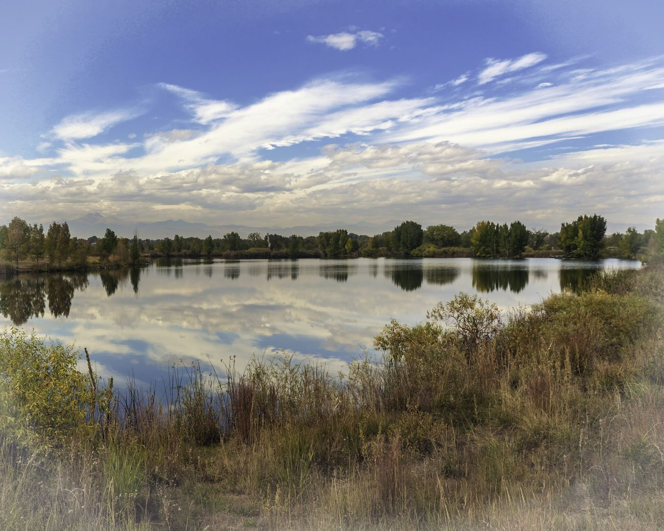 Cloudy sky over small lake at The Saint Verain Park in Longmont Colorado.
