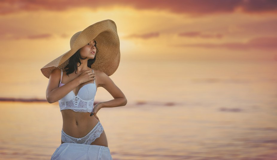 Young beautiful sexy seductive female model pose in white bridal lingerie and big beach hat on t...