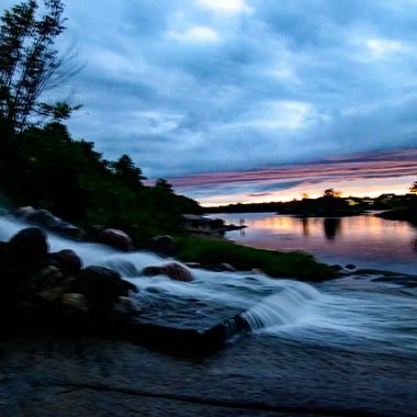 Taken right after a lot of rain which created this beautiful waterfall to the Rainy River at sunset