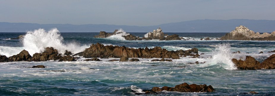 Long rocky shoreline with crashing waves