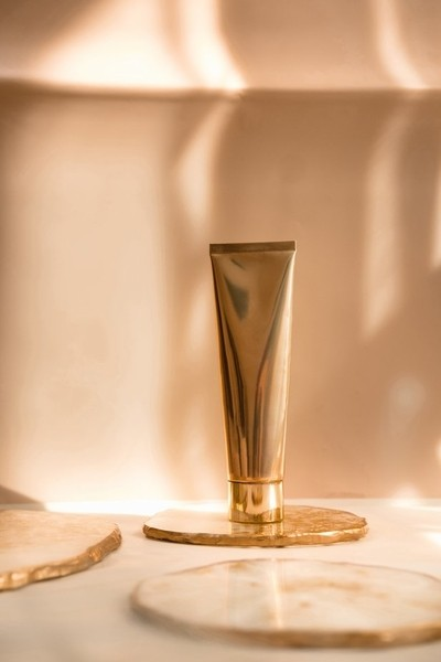 Golden cosmetic tube on pastel color minimalism beauty 02