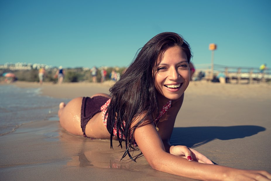 I went to the beach with this beautiful model and she was having a relaxed time from the photoshoot. I surprised her waking her up with the camera on my hands. She smiled spontaneously I and pressed the shutter.