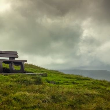 Recycled materials memorial bench with Pendle Hill in background under a storm clouds sky