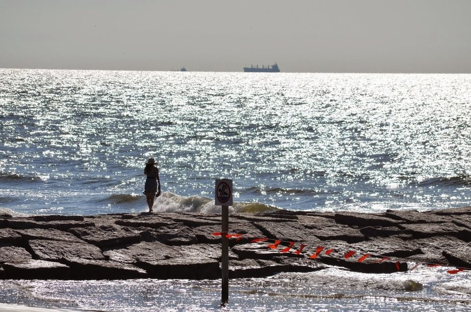 People watching on Galveston Seawall. A woman contemplating, while a freighter passes by.