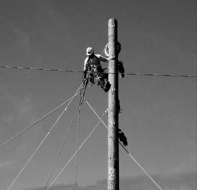 A linesman stringing up new transmission lines. My dad  loved linesmen. He worked for the power company.