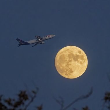 FedEx Cargo Plane taking off from John Wayne Airport, Newport Beach, CA against the rising moon in the early evening at dusk.