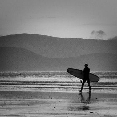 Surfer at sunset on Ireland beach