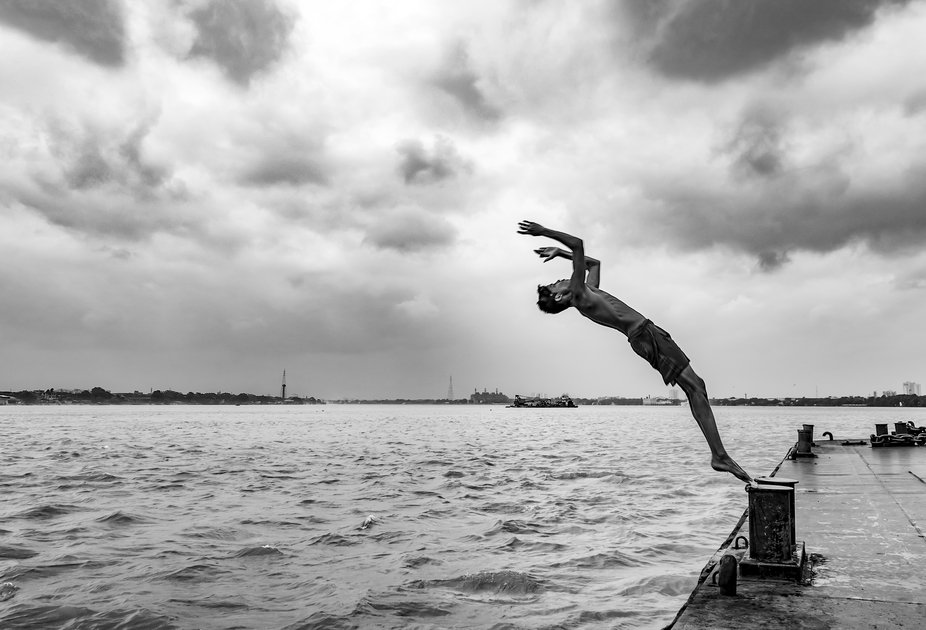 Boy diving in the river from a jetty in the summer