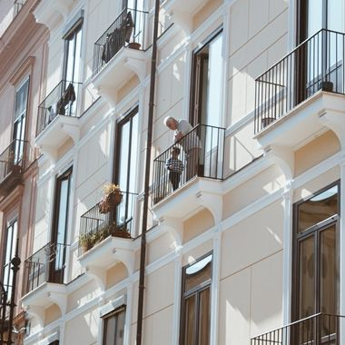 A grandfather and grandson watching the streets from their balcony.