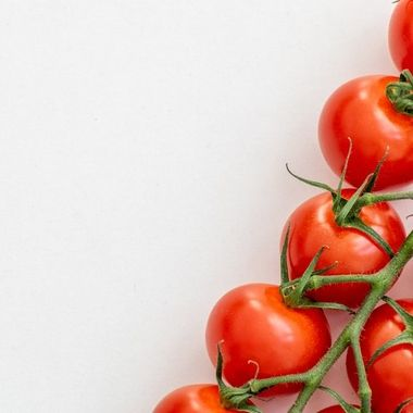 a vine of fresh tasty cherry tomatoes diagonally on a white table