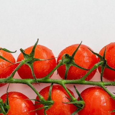 a vine of fresh tasty cherry tomatoes horizontally on a white table
