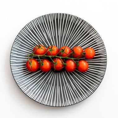 a straight vine of tasty cherry tomatoes on a patterned grey plate
