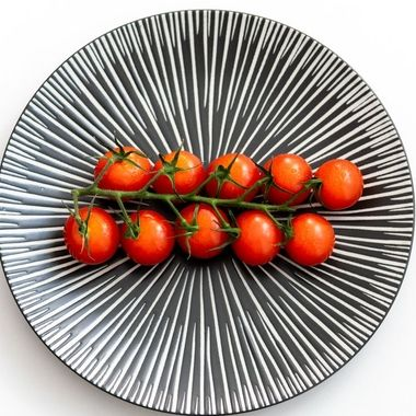 a vine of tasty cherry tomatoes on a patterned grey plate
