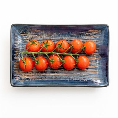 a vine of cherry tomatoes on a blue ceramic rectangle plate