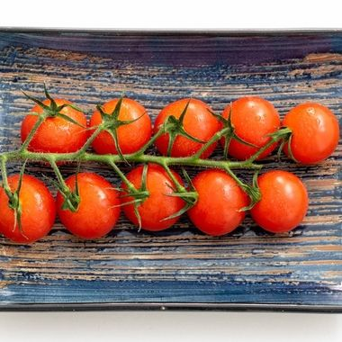 a vine of cherry tomatoes on a blue ceramic rectangle plate close up