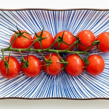 a close up image of a vine of cherry tomatoes on a ceramic rectangle plate with a blue pattern