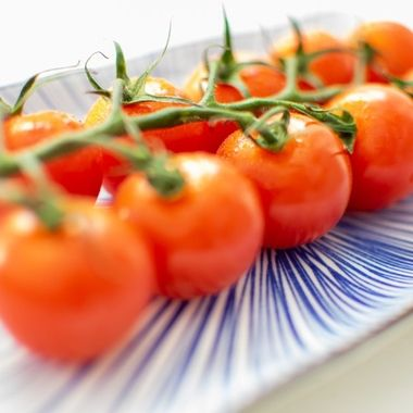 a macro image of a freshly cut vine of cherry tomatoes presented on a blue ceramic plate