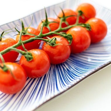 a macro image of a cut vine of cherry tomatoes presented on a blue ceramic plate