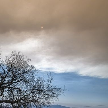 Sun appears like a red dot in the sky behind the cloud generated by the Wildfires.