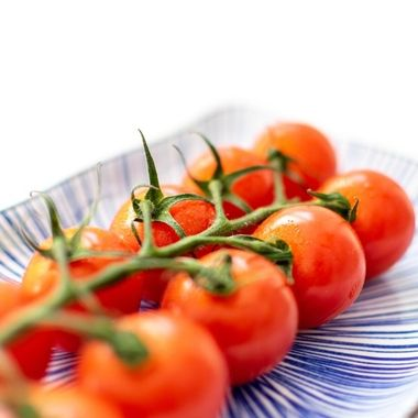 a abstract image of a vine of cherry tomatoes on a ceramic plate with blue pattern
