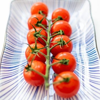 a horizontal vine of cherry tomatoes on a ceramic plate