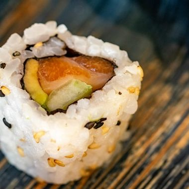 a close up view of a single california sushi roll filled with smoked salmon and avocado on a ceramic plate