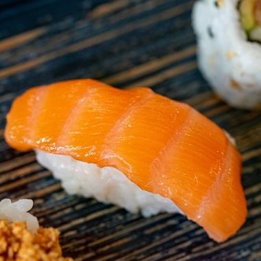 a isolated smoked salmon nigiri sushi among varied sushi pieces