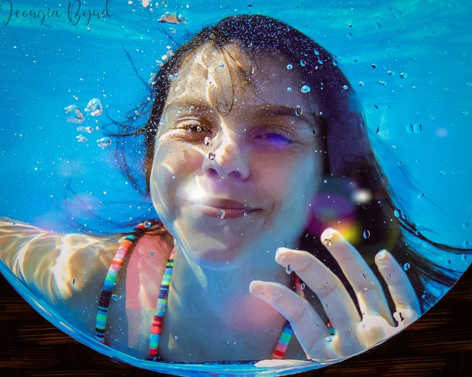 my niece underwater waving at me