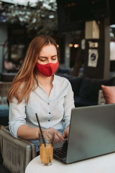 Blonde woman with mask working on laptop