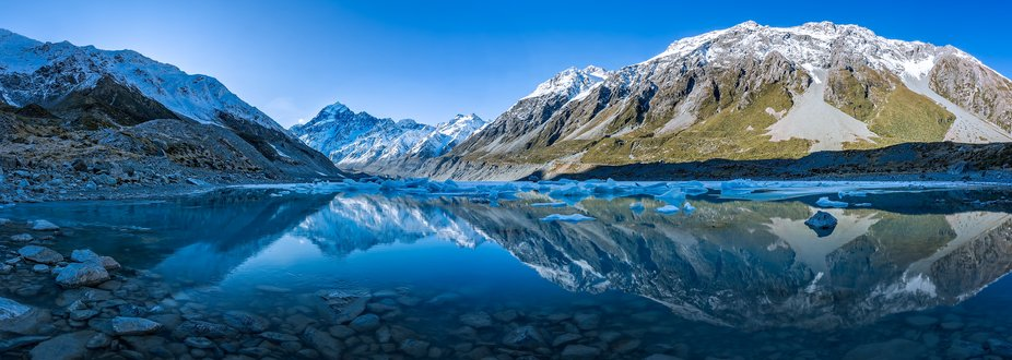 Panorama of Hooker lake with snow capped Mount Cook in the distance reflecting in the lake and a ...