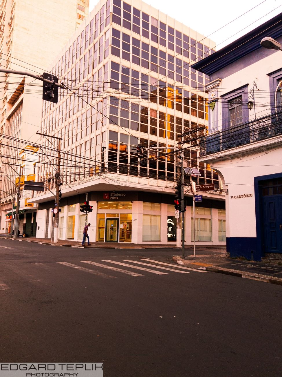 In this photo we have a beautiful contrast between a modern building with a large glass area and an old colonial style house in the center of Campinas