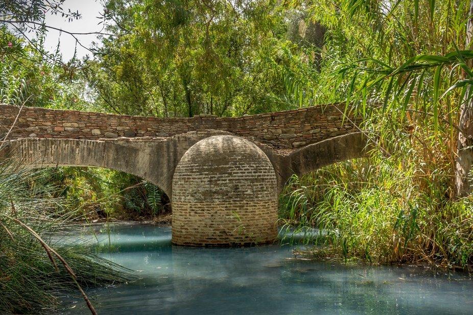 Old stone bridge over the sulphur river located near Roman sulphur baths of Hedionda built by Julius Caesar army