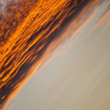 a close up warm diagonal image of golden orange clouds during a sunset in Marbella, Spain