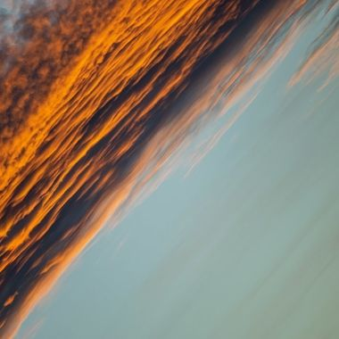a close up cool diagonal image of golden orange clouds during a sunset in Marbella, Spain