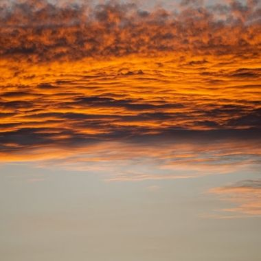 a close up warm horizontal image of golden orange clouds during a sunset in Marbella, Spain