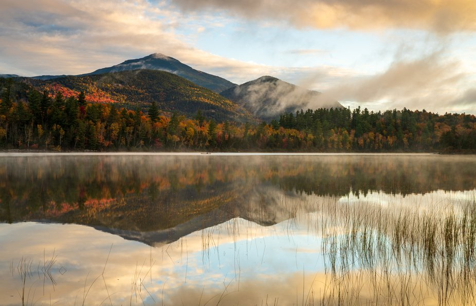 A kayaker enjoys an early morning paddle among Whiteface reflections and mist in the Adirondacks
