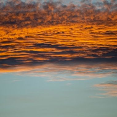 a close up cool horizontal image of golden orange clouds during a sunset in Marbella, Spain