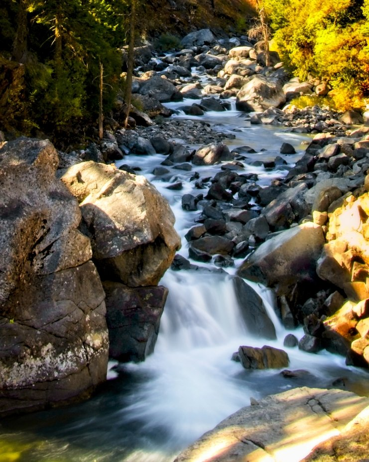 Fall is here in Leavenworth, Washington. A small falls with colorful trees in Icicle Creek.